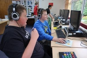 Two members of our radio group work on their podcast with headphones at the computers