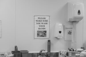 Image of a sink in a kitchen with a sign above the sink reading Please make sure you wash your hands in large lettering